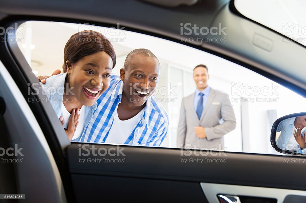 african couple choosing luxury car stock photo