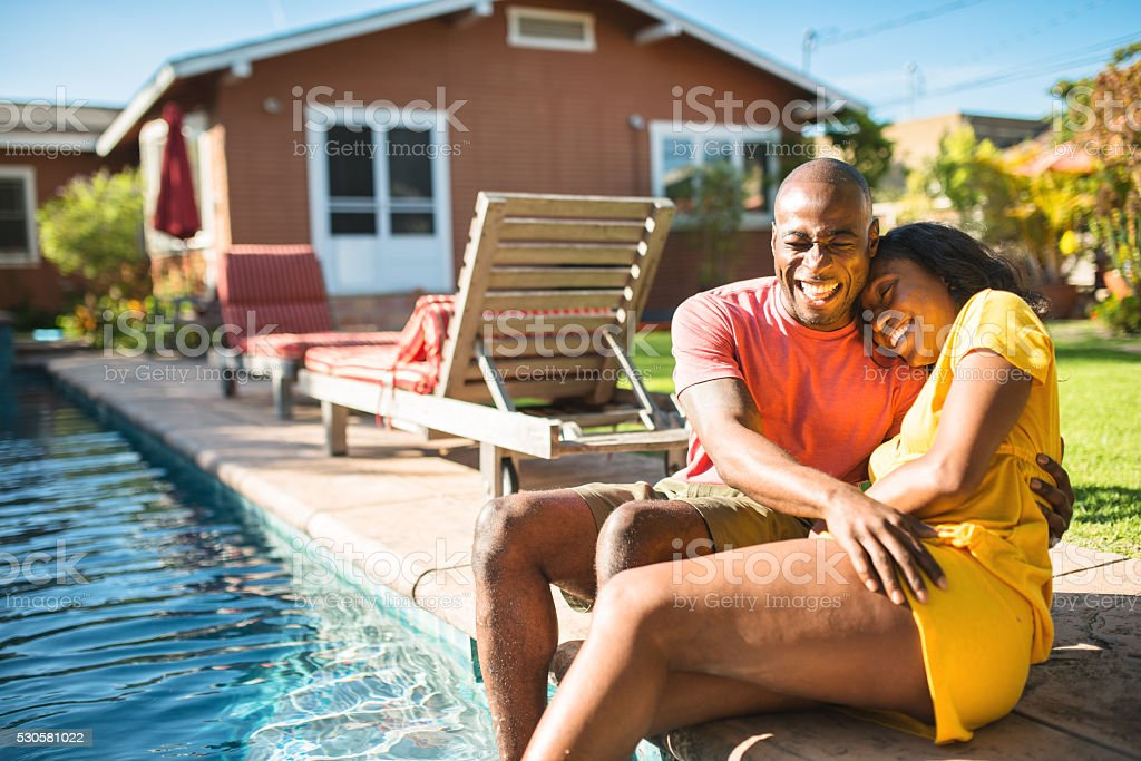 african couple enjoy in the house courtyard at the poolside stock photo