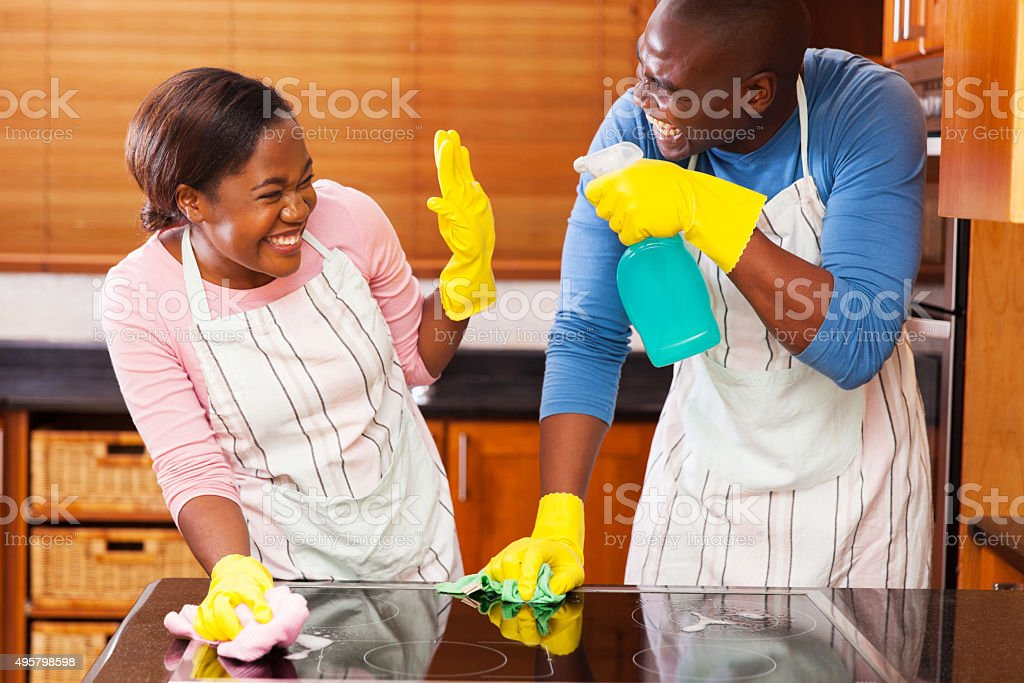 african couple having fun while doing household chores stock photo