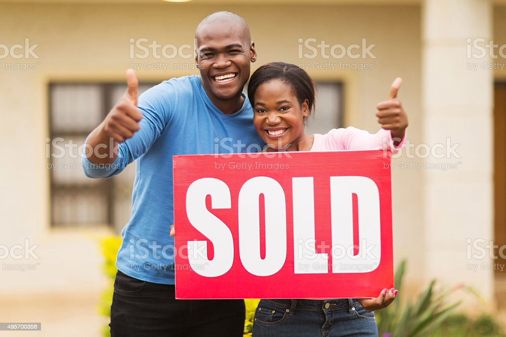 african couple outside home with sold sign stock photo