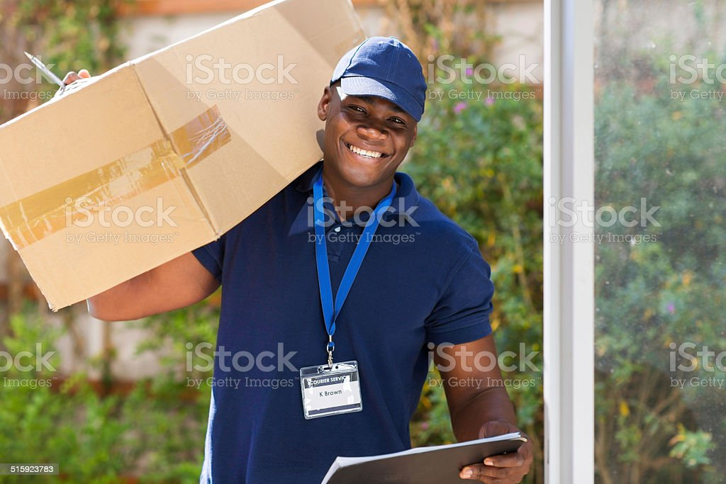 african courier standing with parcel at the door stock photo