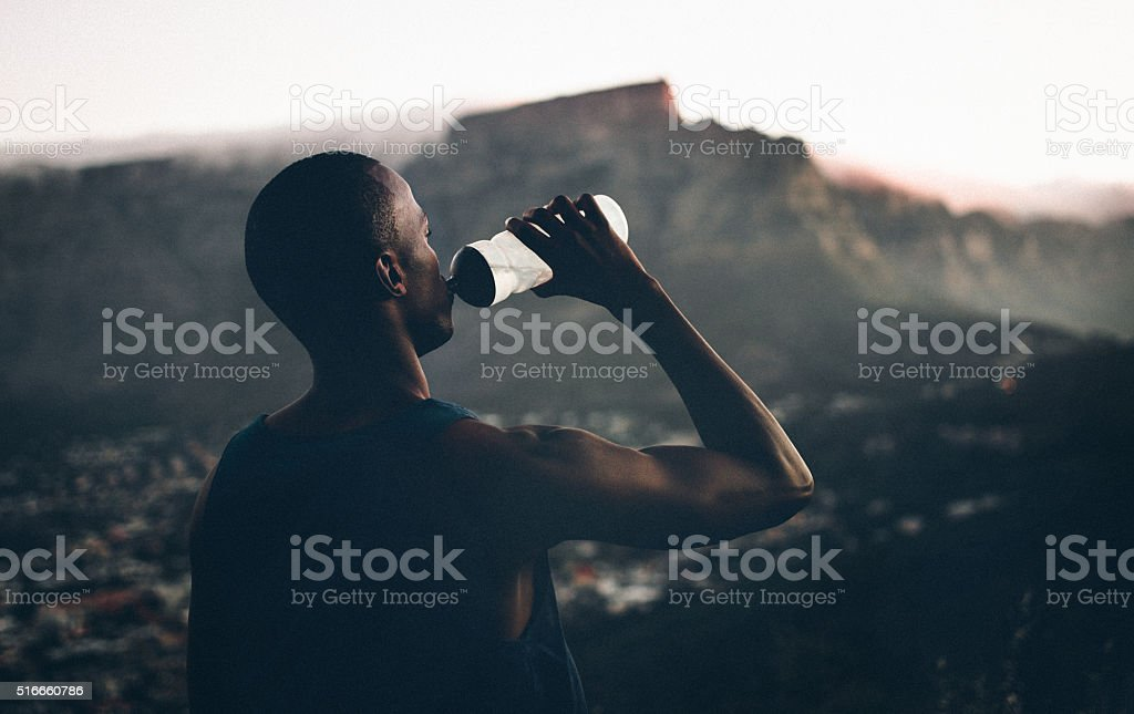 African decent athlete drinking water after a fitness achievemen stock photo