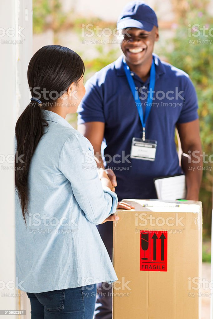 african delivery man handshaking with customer stock photo