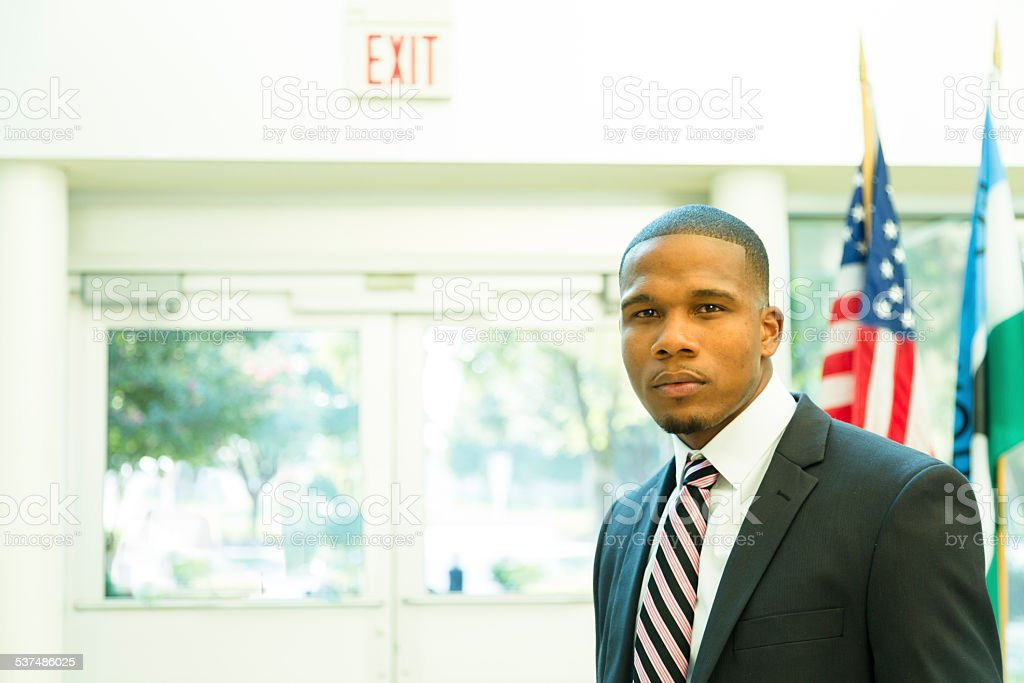 African descent attorney, politician in courthouse building. American flag. Suit. stock photo
