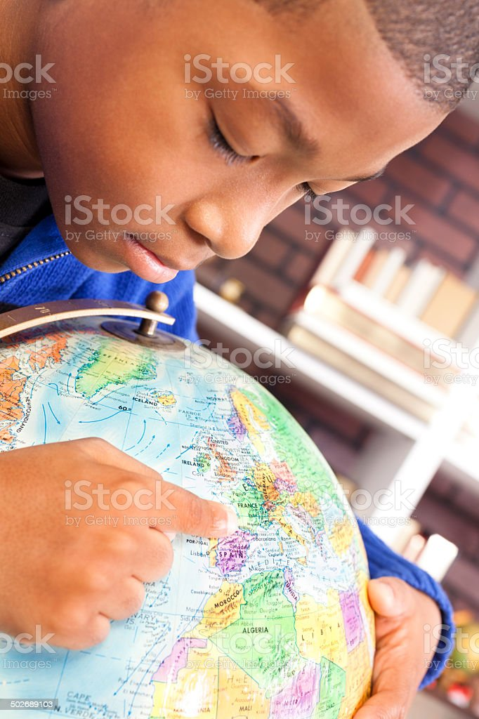 African descent boy enjoys discovering new countries. Globe. stock photo