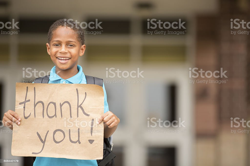 African descent boy, student holds 'thank you' sign. School. Education. stock photo