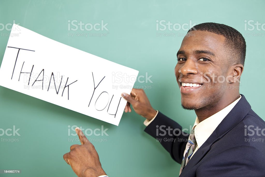 African descent business man holds 'Thank You' sign. Suit, tie. royalty-free stock photo