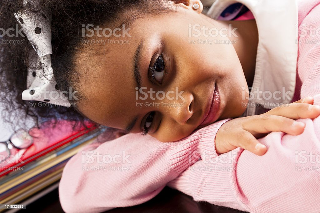 African descent elementary girl 7-8 laying head on desk royalty-free stock photo