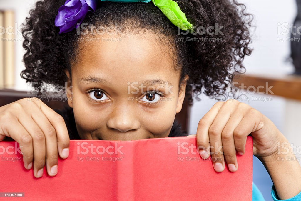 African descent, elementary student girl. Peeking book. School library. Reading. royalty-free stock photo