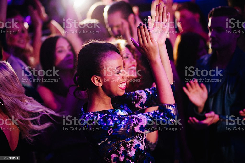 African descent girl enjoys dancing with friends in nigh club stock photo