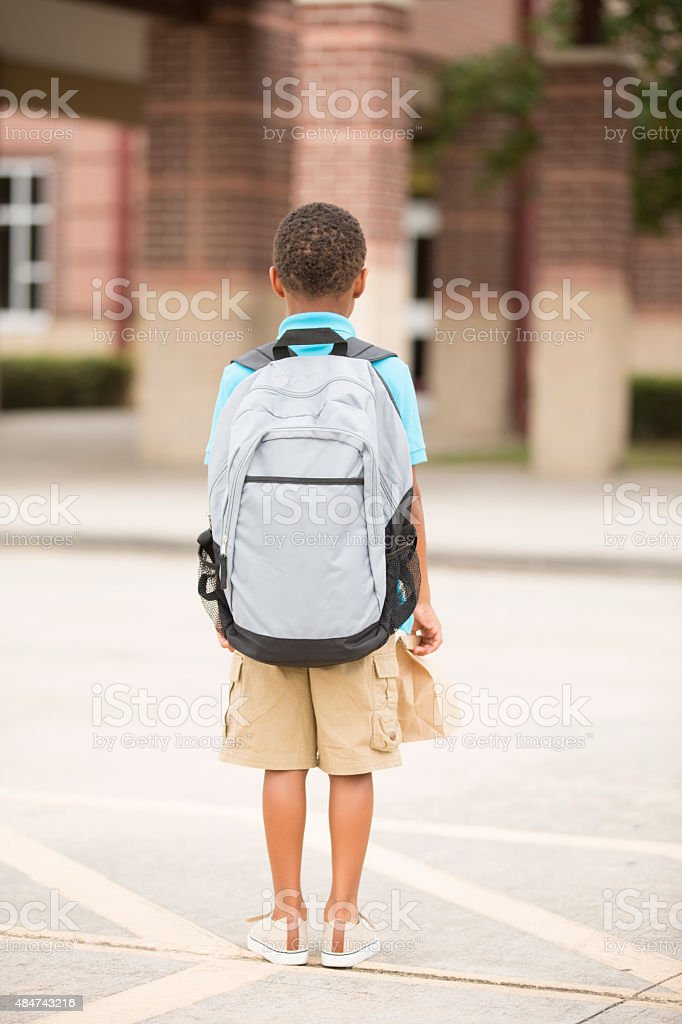 African descent, little boy faces school building. Lunch, backpack. stock photo