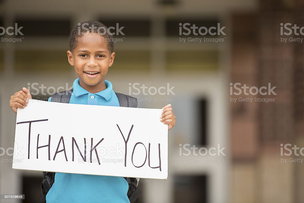 African descent, little boy holds 'thank you' sign. School. stock photo