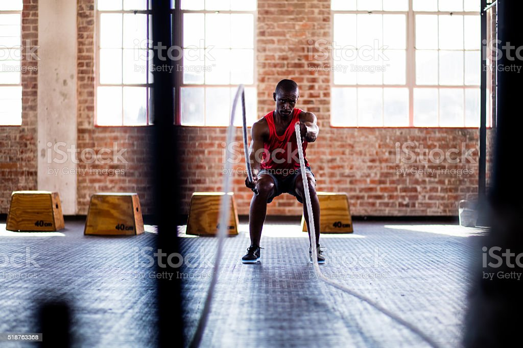 African descent man doing battle rope exercise in cross training stock photo