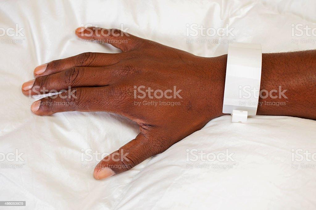 African descent man's hand. He wears hospital identification bracelet. stock photo
