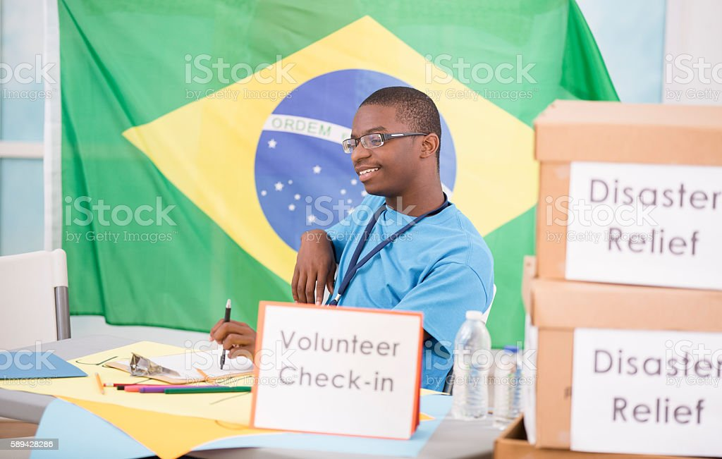 African descent teen boy registers at volunteer check-in table. stock photo