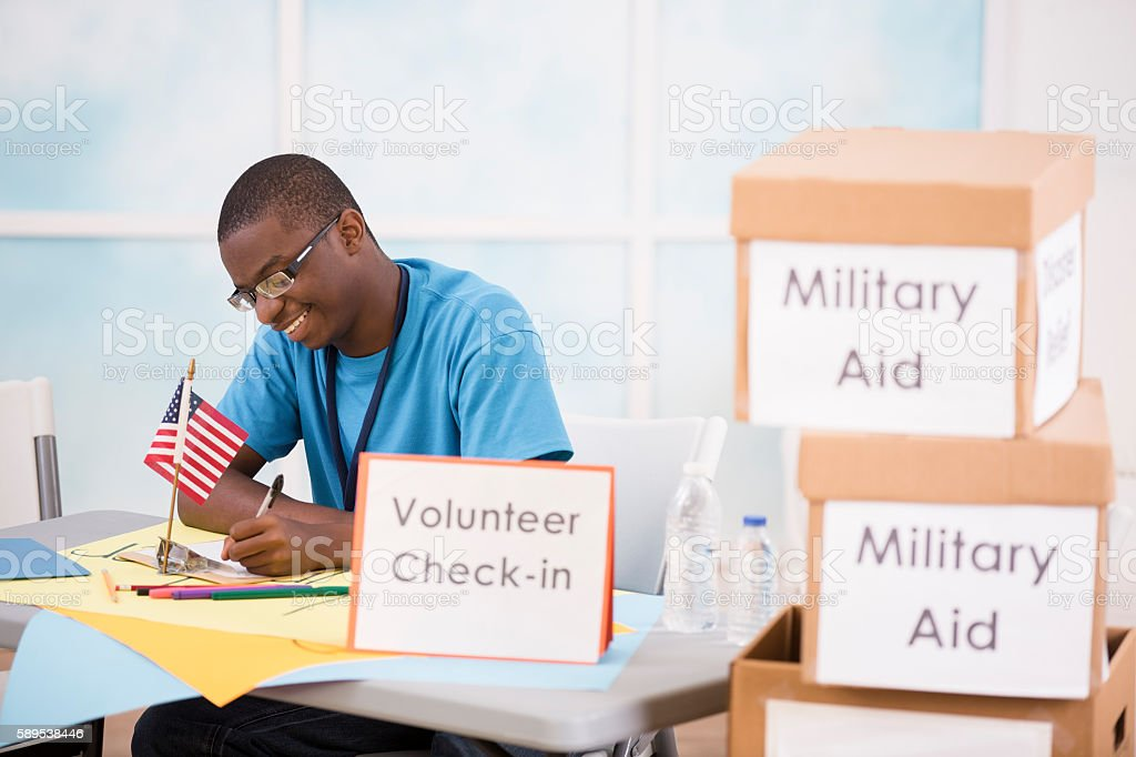 African descent teen boy volunteers with American military aid. stock photo