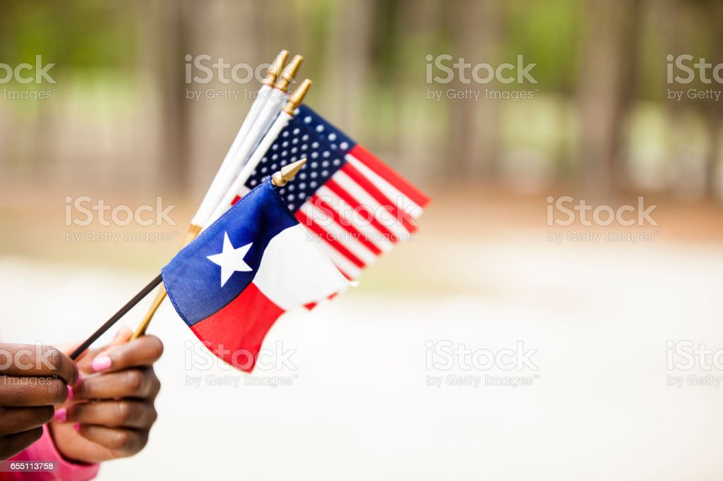 African descent woman holding Texas, USA flags. stock photo