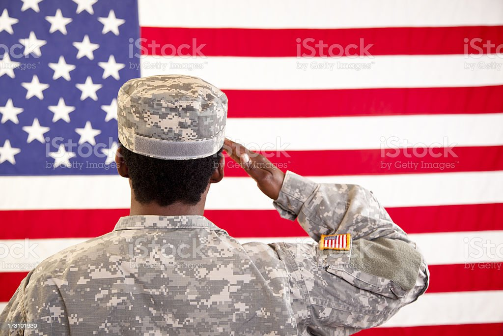 African descent woman in military uniform saluting American flag. stock photo