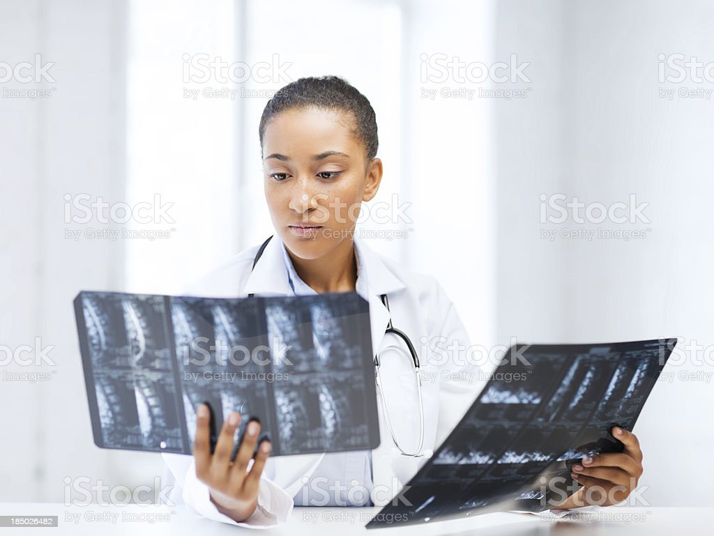african doctor looking at x-rays stock photo