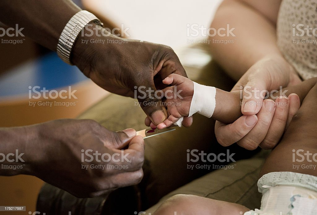 African doctor taking blood from baby stock photo