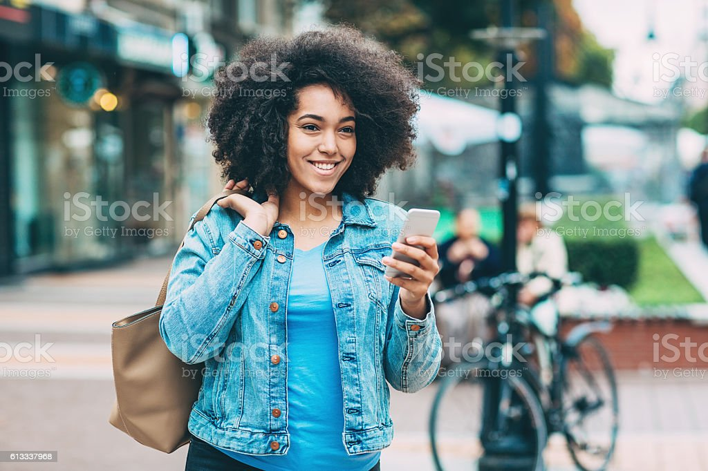 African Ethicity girl with smart phone walking on the street stock photo