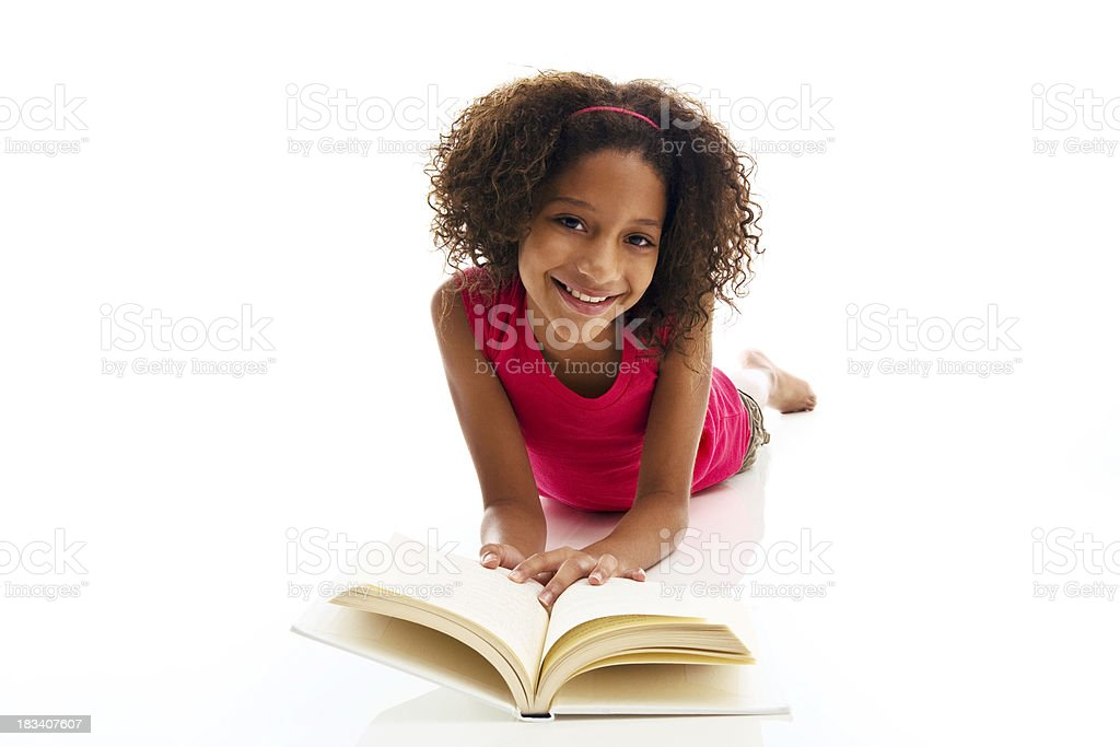 African ethnicity girl lying on front reading book royalty-free stock photo