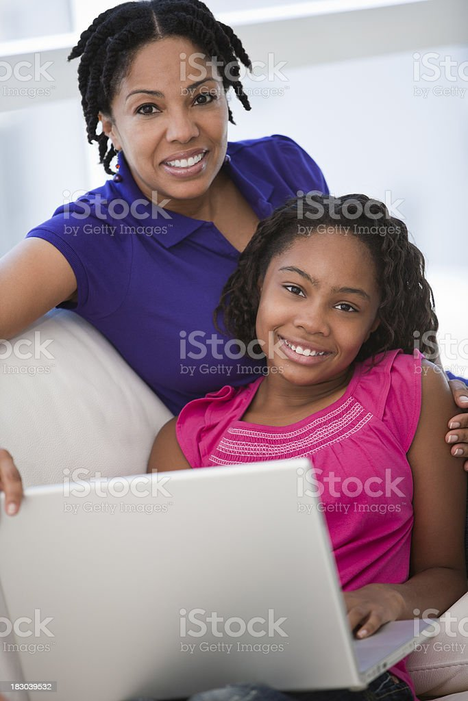 African ethnicity mother and daughter with laptop stock photo
