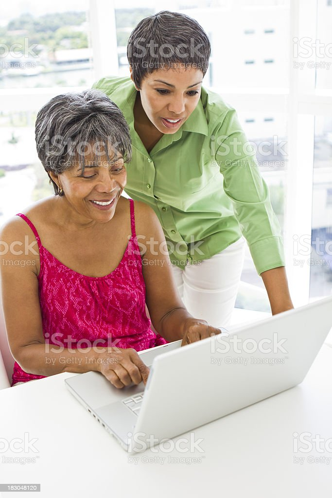 African ethnicity senior and mid adult female looking at labptop royalty-free stock photo