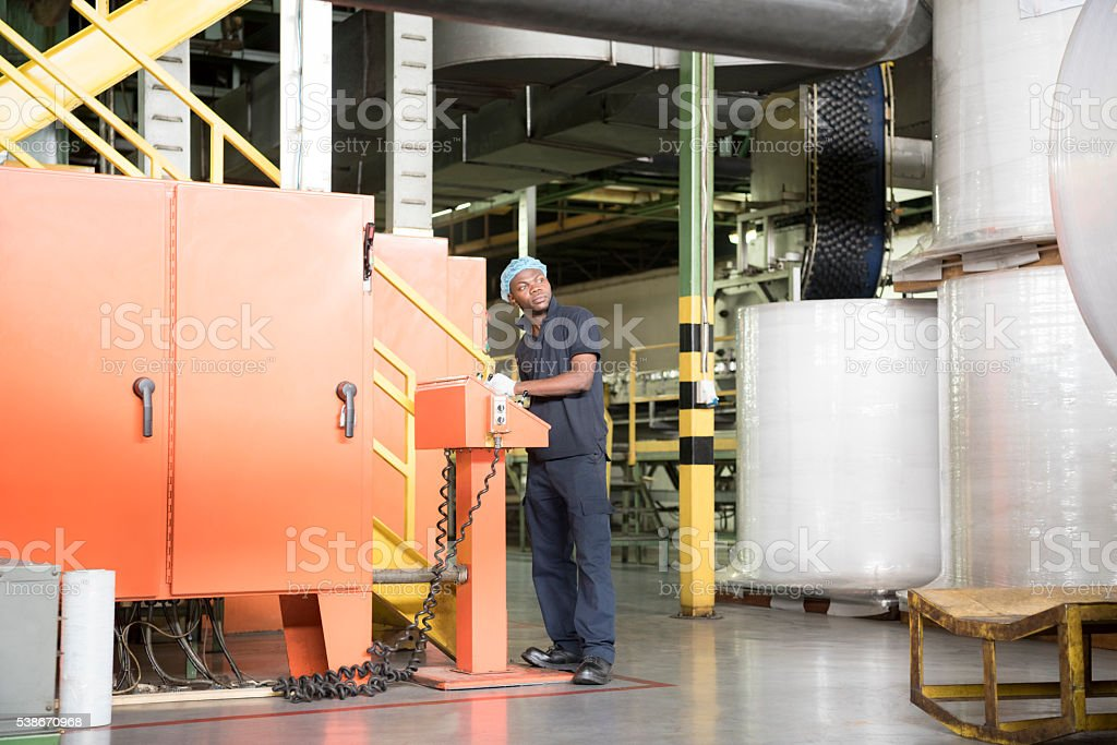 African factory worker operating machinery at aluminium can production facility stock photo