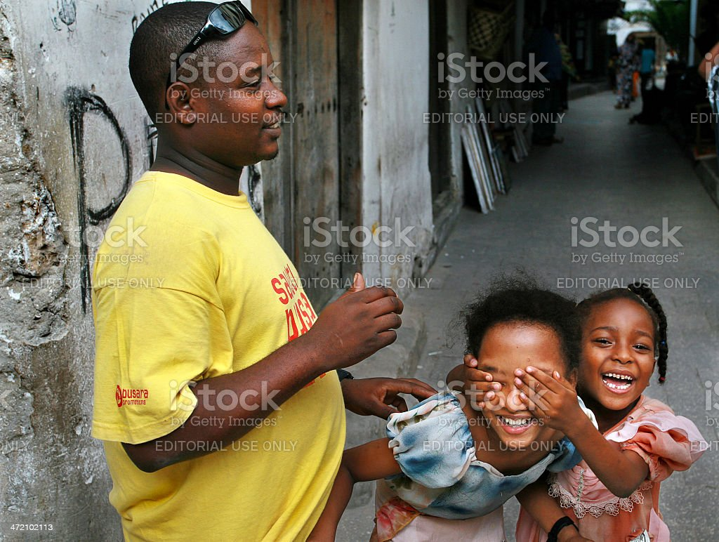 African family, black man and two dark-skinned girls, kids play. stock photo