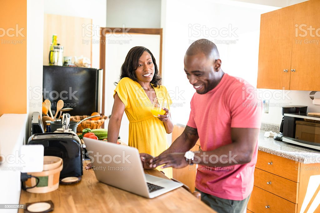 african family doing the breakfast on the pc stock photo
