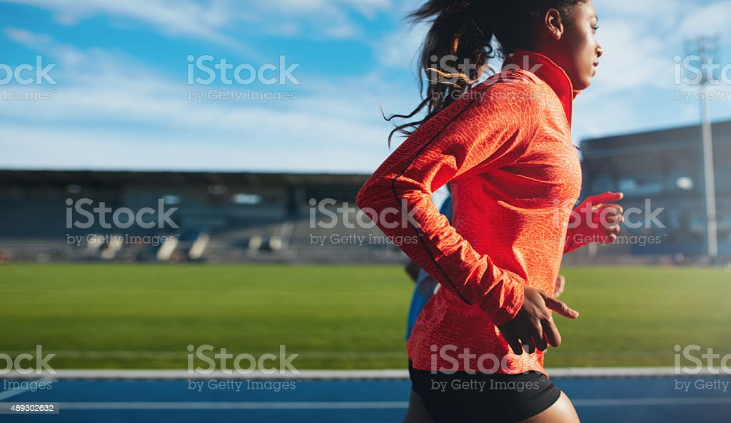 African female athlete training on race track stock photo
