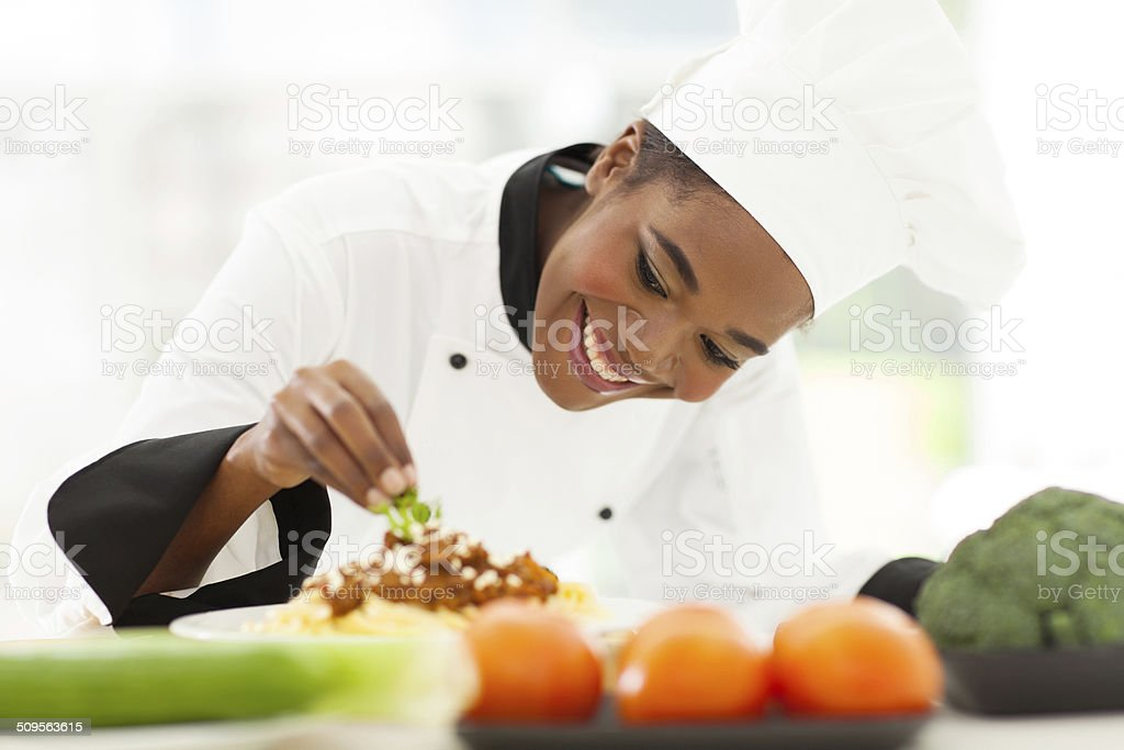 african female chef garnishing spaghetti dish stock photo