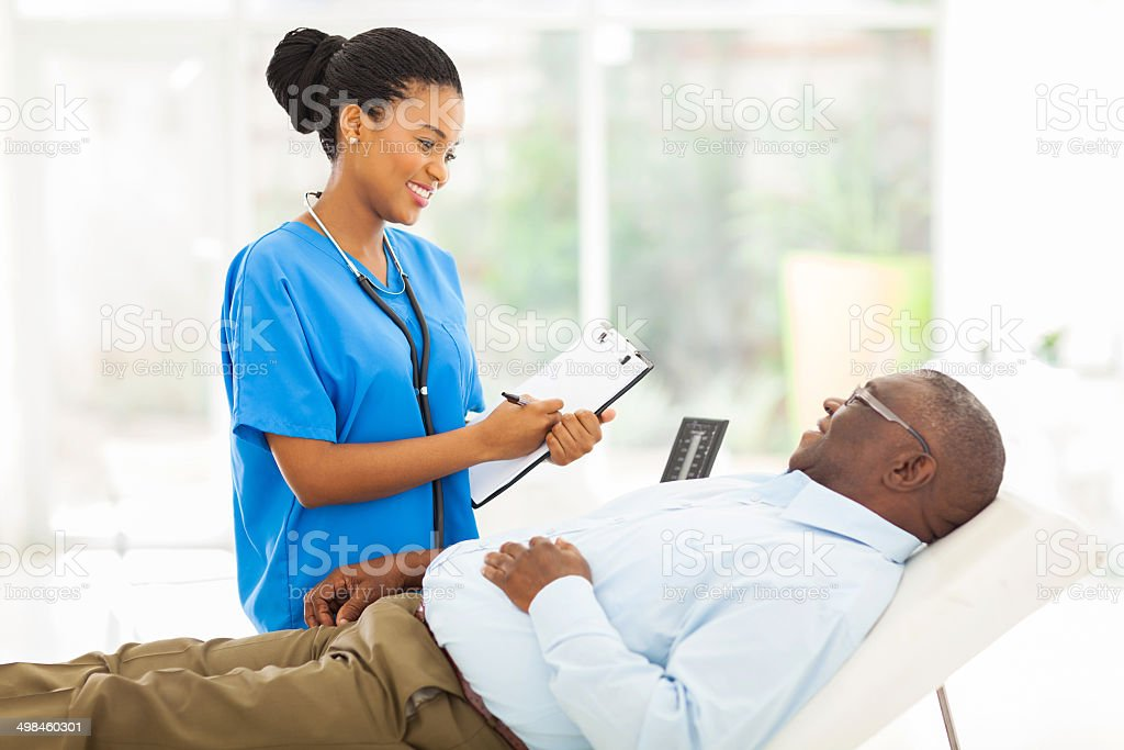 african female doctor consulting senior patient stock photo