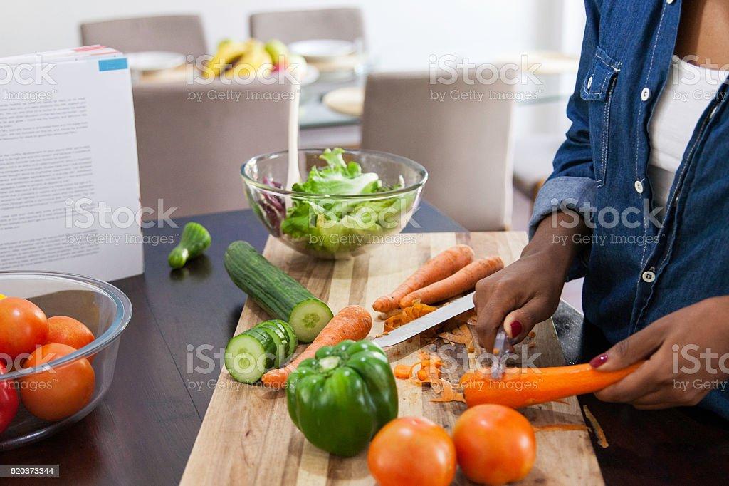 African female peeling carrots. stock photo