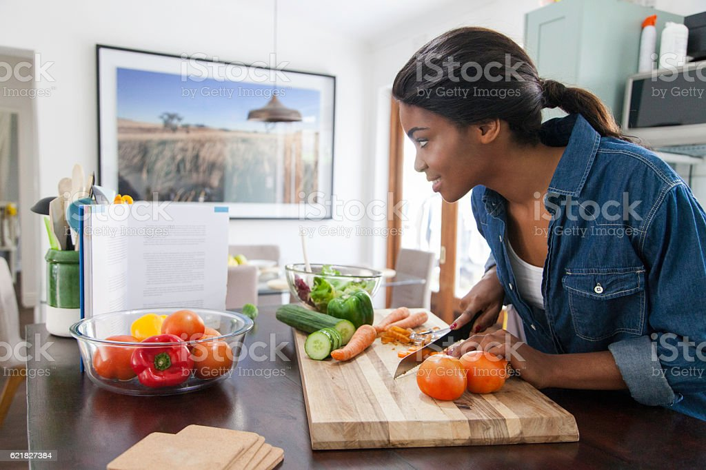 African female reading from a cookbook while chopping carrots. stock photo