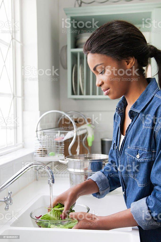 African female rinsing lettuce. stock photo