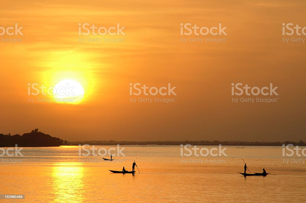 African fishermen in canoes at sunset royalty-free stock photo