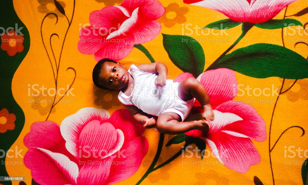 African five months old baby lying on flower-patterned bed stock photo