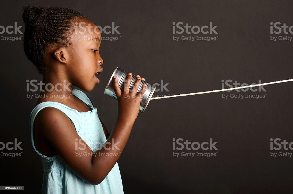 African girl communicating through a tin stock photo