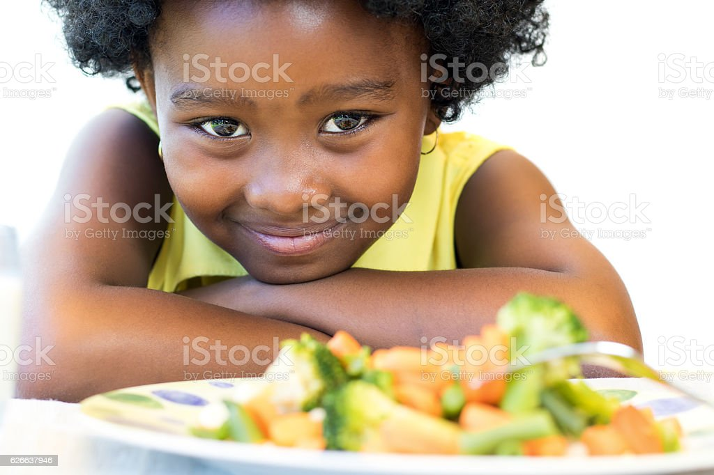 African girl in front of vegetable dish. stock photo