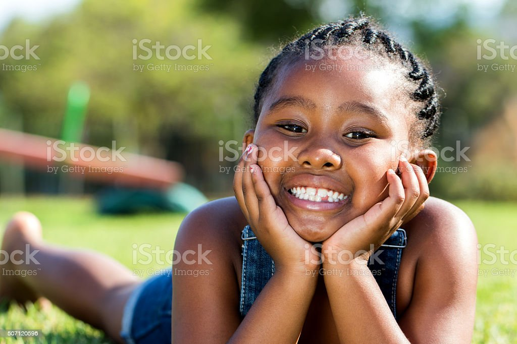 African girl laying with face on hands in park. stock photo