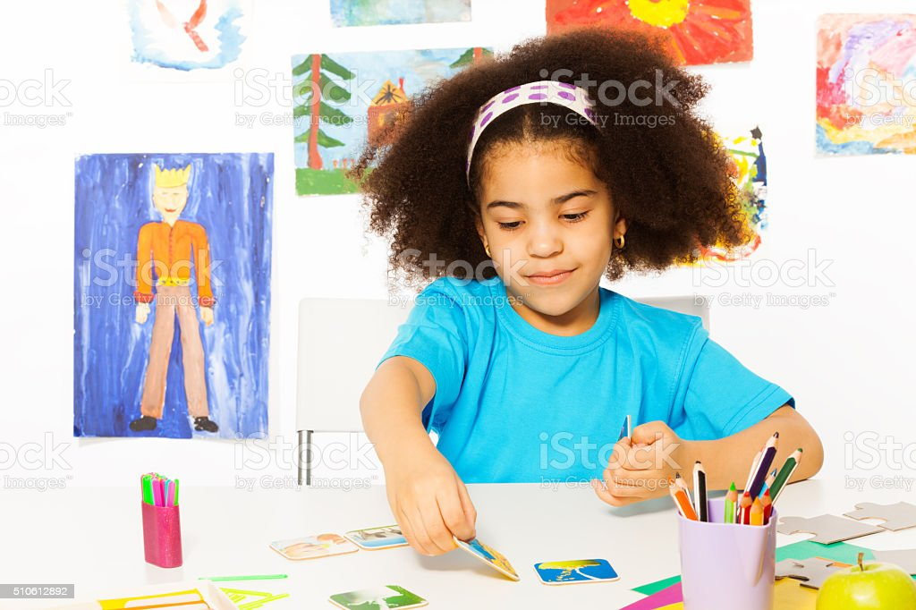 African girl plays developmental game putting card stock photo