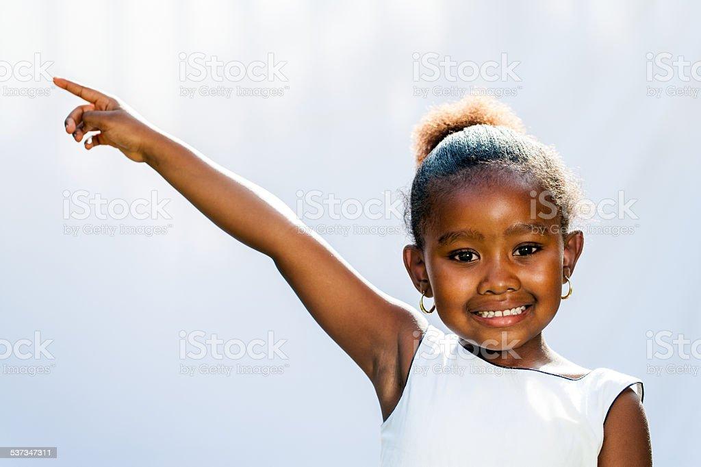 Jeune fille africaine avec doigt pointant à l'angle. photo libre de droits