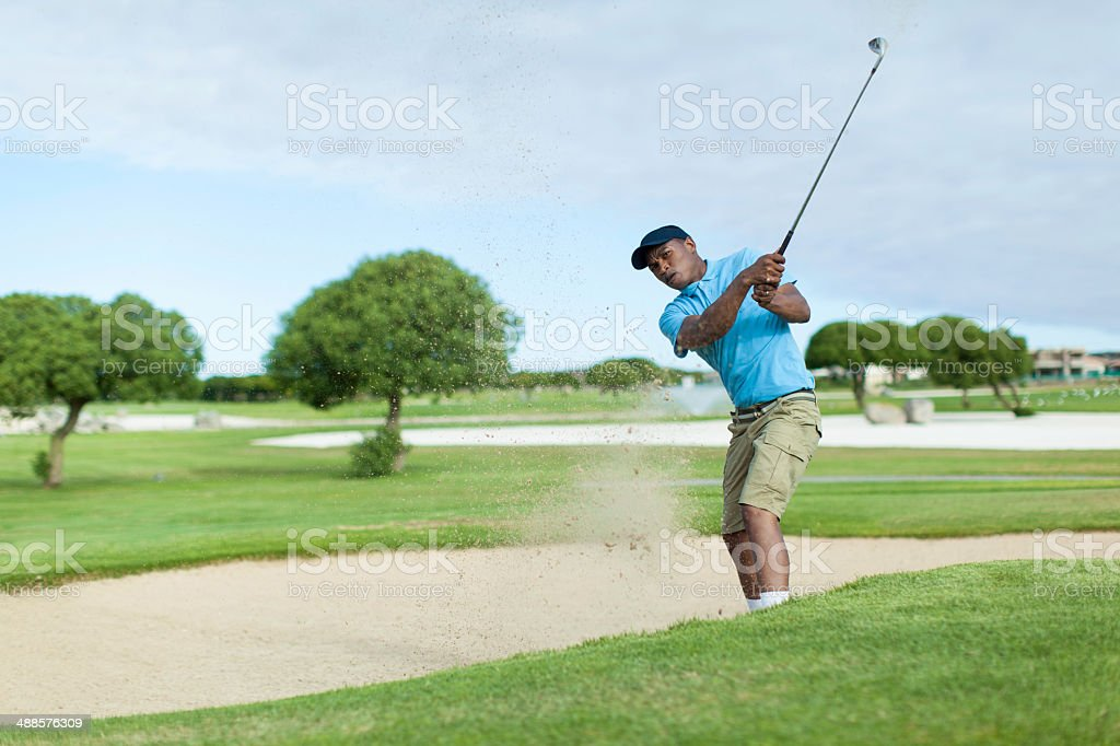 African golfer getting his ball out of the bunker. stock photo