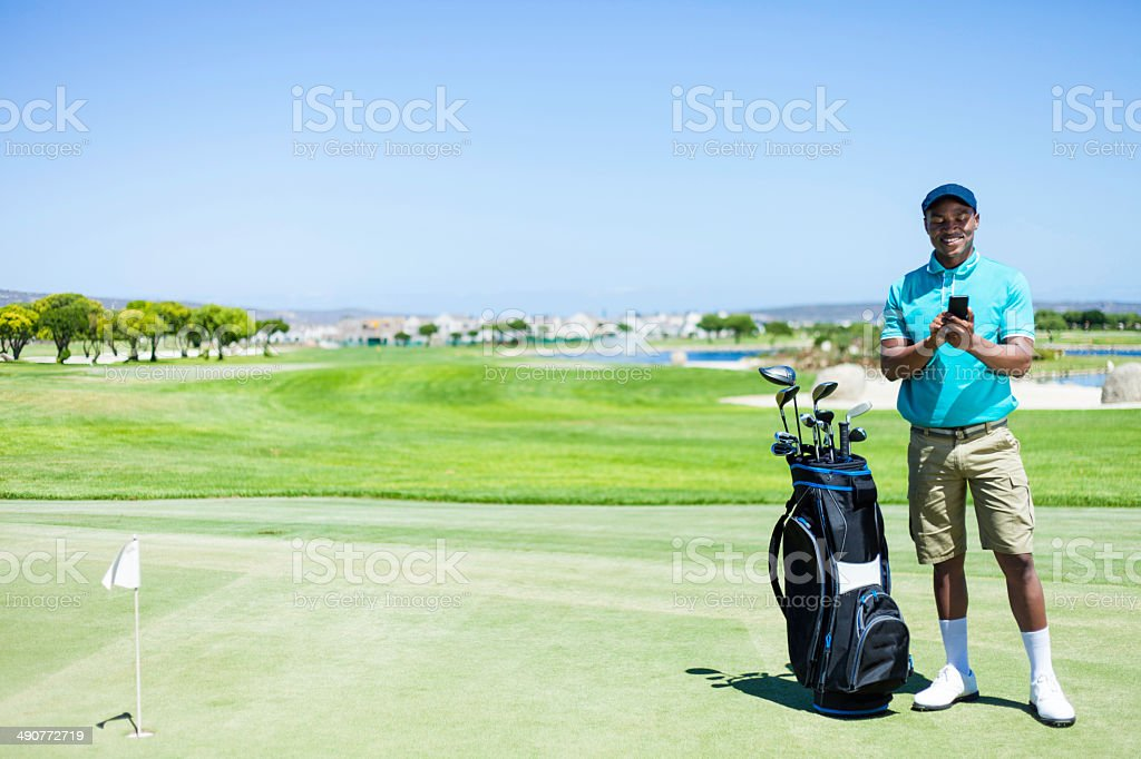 African golfer typing on his phone, smiling. stock photo