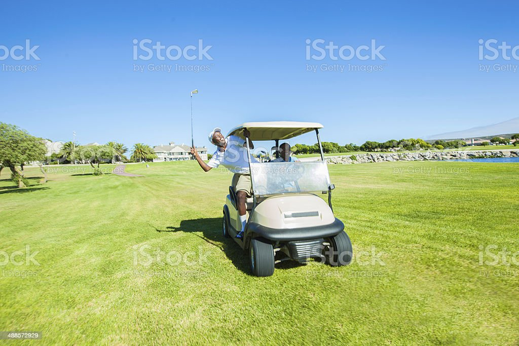 African golfers on a joy ride having fun royalty-free stock photo