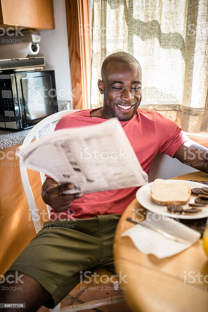 african guy doing breakfast and reading the newspaper stock photo
