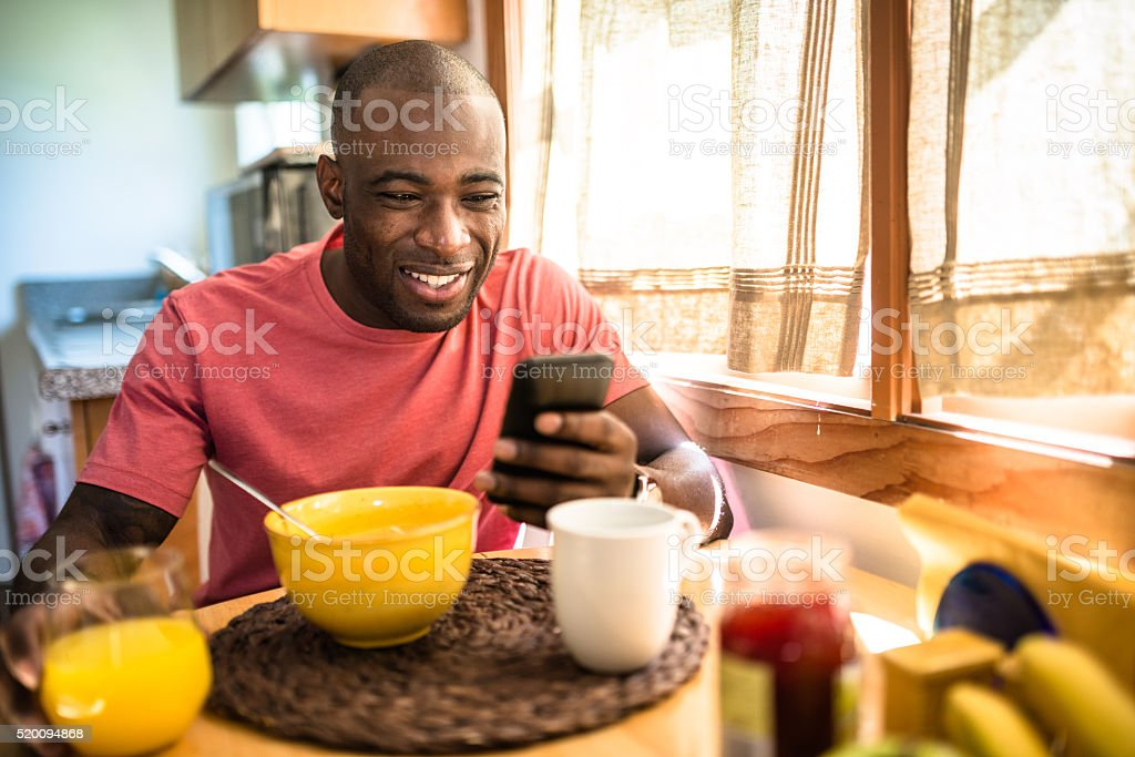 african guy doing breakfast at home stock photo