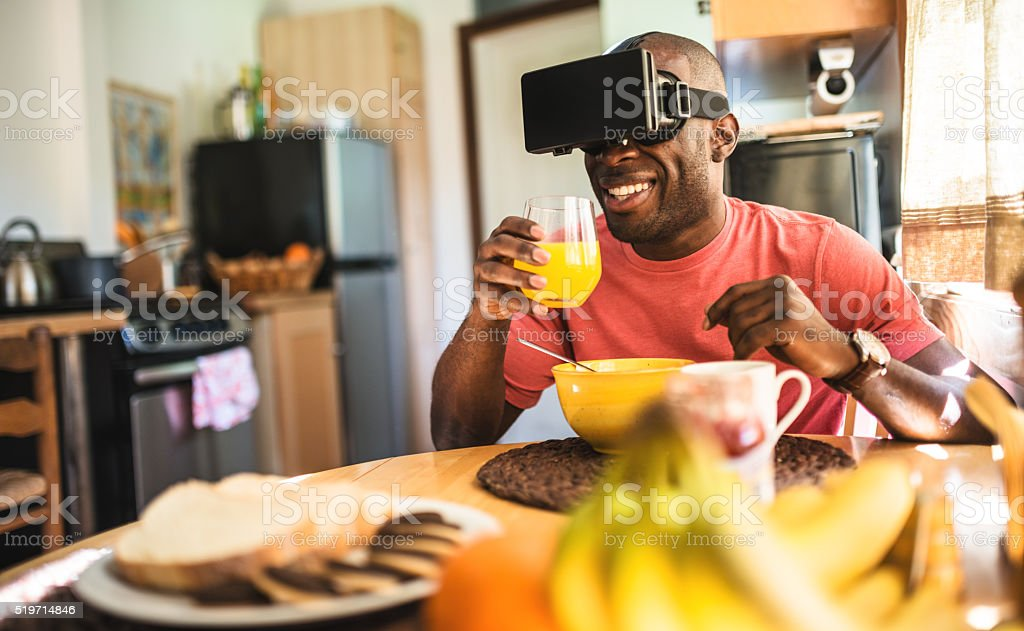 african guy entartains his self with virtual reality device simulator stock photo